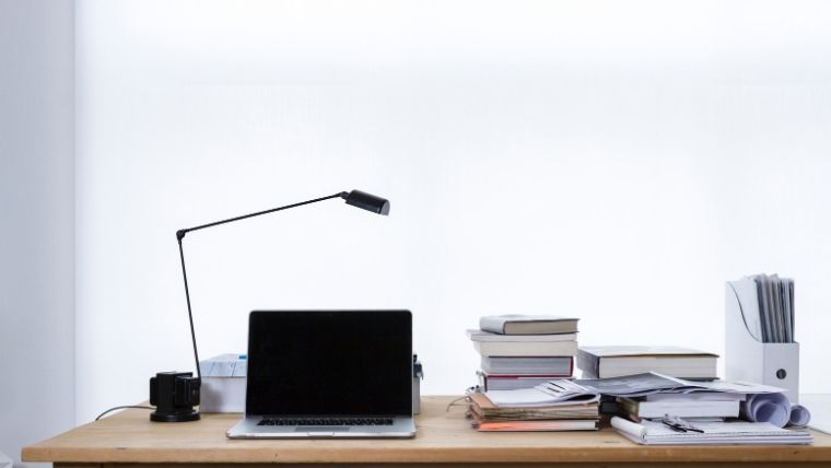 office desk with laptop and books
